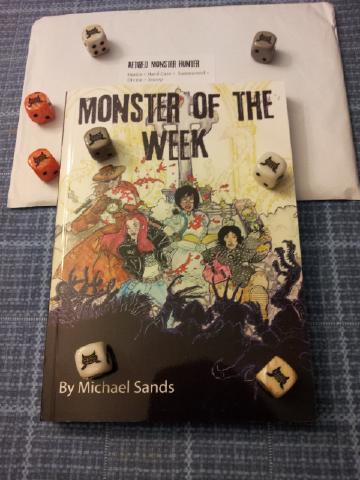 A digest sized role-playing book with scattered about. The cover is of four women fighting shadowy monsters.