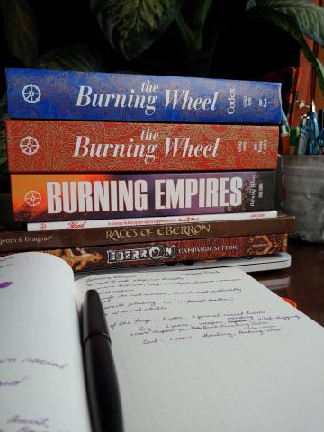 "A pile of books: ""Burning Wheel Codex,"" ""Burning Wheel Gold Revised,"" ""Burning Empires,"" ""Jihad: Burning Sands,"" ""Races of Eberron,"" and ""Eberron Campaign Setting."""