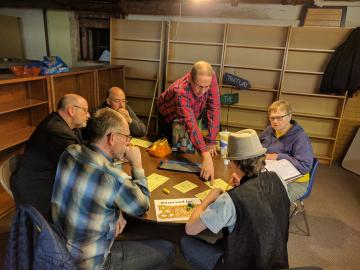 Six people around a circular table with dice and character sheets