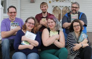 Three women and three men sitting on steps each lovingly holding their favorite books.