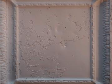 A matte-white painted tin ceiling tile
