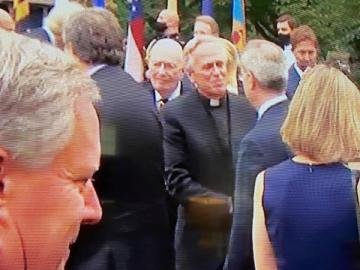 Father Jenkins, maskless and amongst a crowd, shaking hands with another maskless middle-aged white person.  The other person's back faces the camera, only the side of their face can be seen.