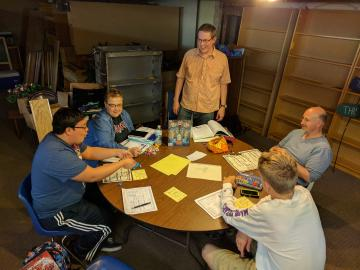 In a basement, four people sit around a table while a fifth stands. Spread across the table are rulebooks, dice, character sheets, and pencils.