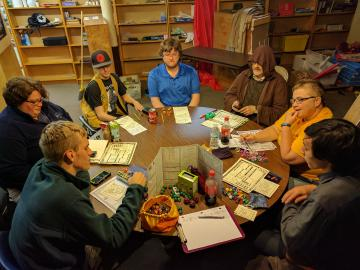Seven people gathered around a table with character sheets, books, and dice.