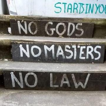 Painted on concrete steps the words: No Gods, No Masters, No Law