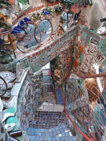 Looking from the top of a stairwell, down the steps.  The walls and steps are made and decorated with plaster and found objects such as bathroom tiles, glass bottles, copper pipes, etc.
