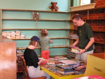 Three people working to sort books and put them on shelves.
